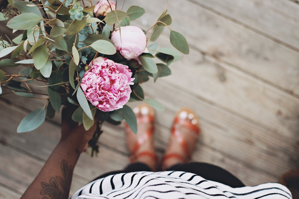 Woman holding flower: How to keep a relationship alive